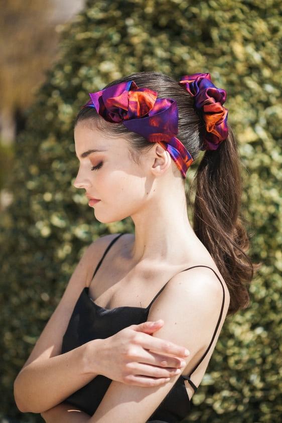 Kοπέλα φοράει χειροποίητο μεταξωτό scrunchie στα μαλλιά της